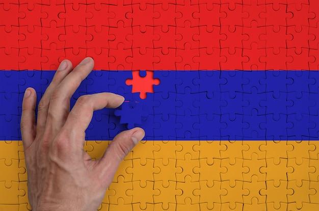 Die armenische flagge ist auf einem puzzle abgebildet, das der mann mit der hand zu falten versucht