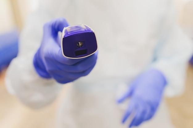 Die arzthand in einem schutzhandschuh hält ein infrarot-thermometer und misst die temperatur des patienten. fernmessung von hohem fieber bei einem coronovirus-patienten während einer pandemie.