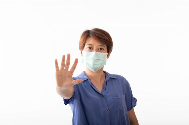Die aseptische medizinische maske einer asiatischen frau, die auf ihrem gesicht und ihren händen geschützt war, blieb ohne anzeichen stehen. luftverschmutzung, viren, das konzept der pandemie des coronavirus