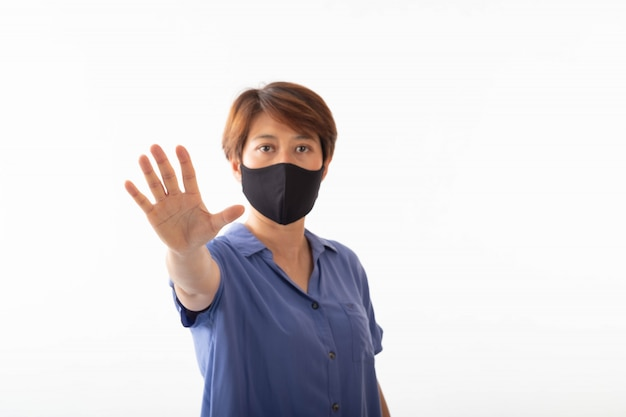 Die aseptische medizinische maske einer asiatischen frau, die auf ihrem gesicht und ihren händen geschützt war, blieb ohne anzeichen stehen.