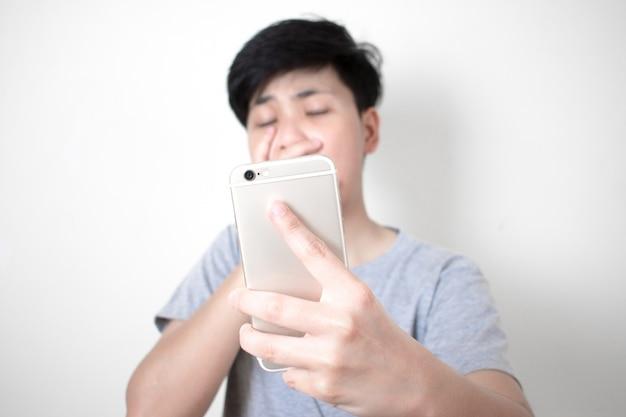 Die asiaten tragen ein graues t-shirt, das beim betrachten der nachricht auf dem smartphone schockiert ist.