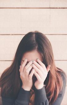 Die asiatin, die allein und deprimiert sitzt, hören auf, häusliche gewalt, gesundheitsangst, das schlechte frustrierte erschöpfte gefühl der leute unten zu missbrauchen