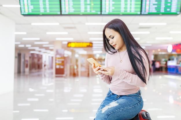 Die asiatin, die auf dem gepäckgebrauch des handys sitzt, überprüfen herein on-line-kartenfluglinie am internationalen flughafen.