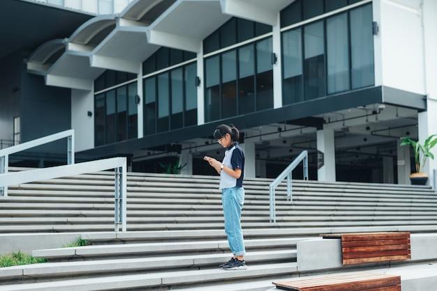 Die asiatin, die auf dem treppenhaus benutztem intelligentem telefon steht, liest