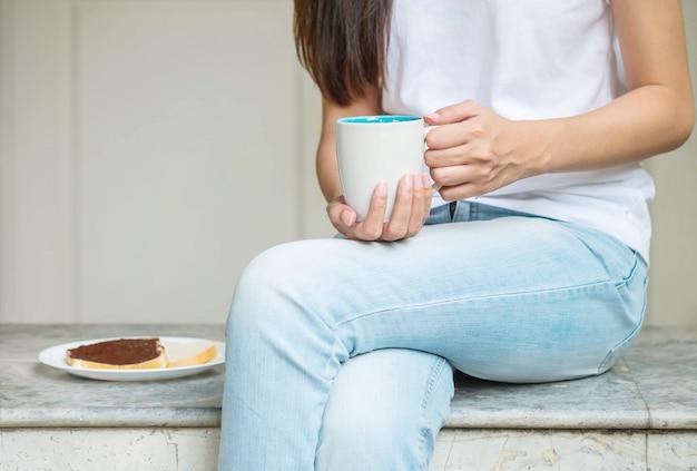 Die asiatin, die auf marmorstuhl vor haus für sitzt, frühstücken morgens