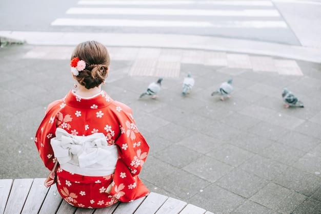 Die asiatin, die das entspannende sitzen des traditionellen japanischen kimonos unter dem baum kyoto trägt, erfahren japan-kultur