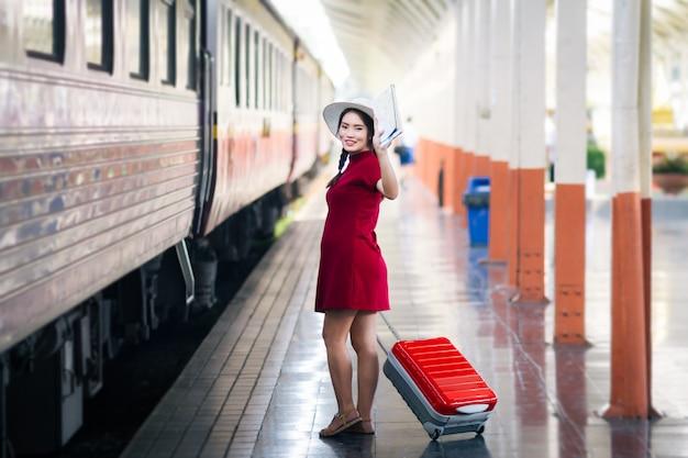 Die asiatin, die im roten kleid schwanger ist, das eine karte und hand hochhält, sagen hallo mit rotem koffer in der eisenbahn