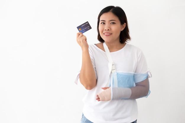 Die asiatin, die kreditkarte hält und setzte an eine weiche schiene