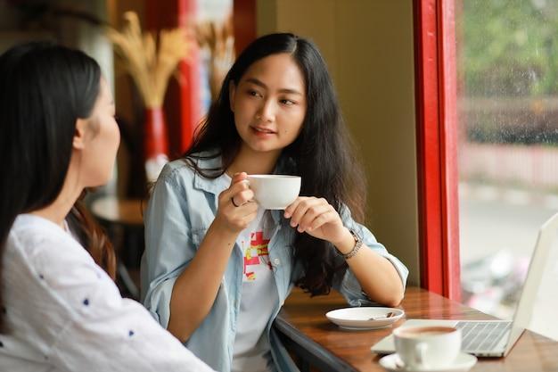 Die asiatin, die laptopfunktion verwendet und trinken kaffee im café