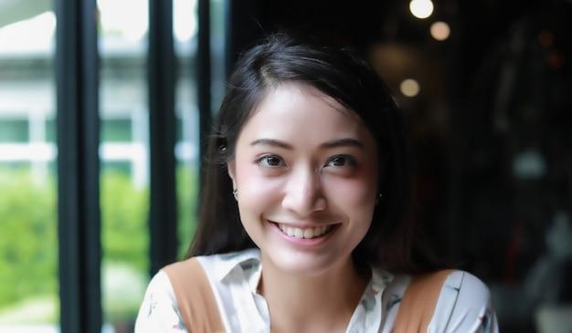 Die asiatinnen, die an lächeln und glücklich und am kaffee und am restaurant genossen, entspannen sich zeit