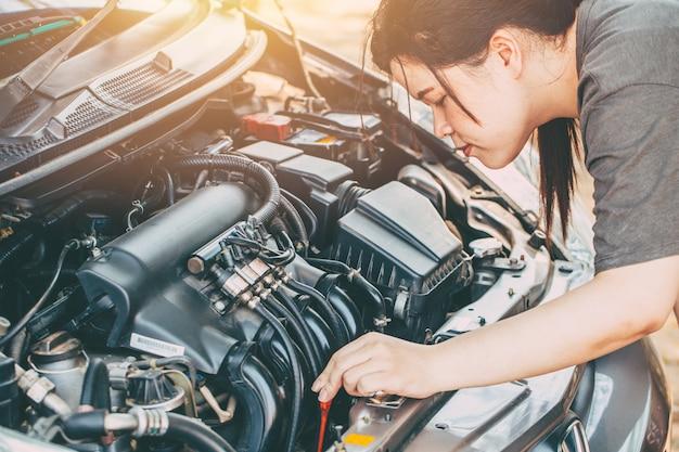Die asiatinnen, die auto lpg-motor überprüfen, bevor gehen reiseweinlesefarbton