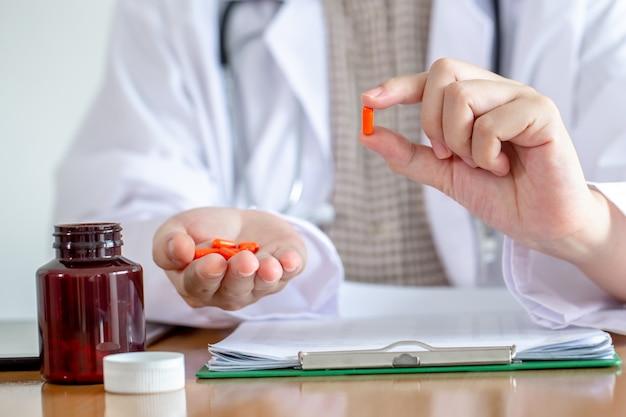 Die asiatische ärztin stellen medizinflasche dem patienten in der klinik vor.
