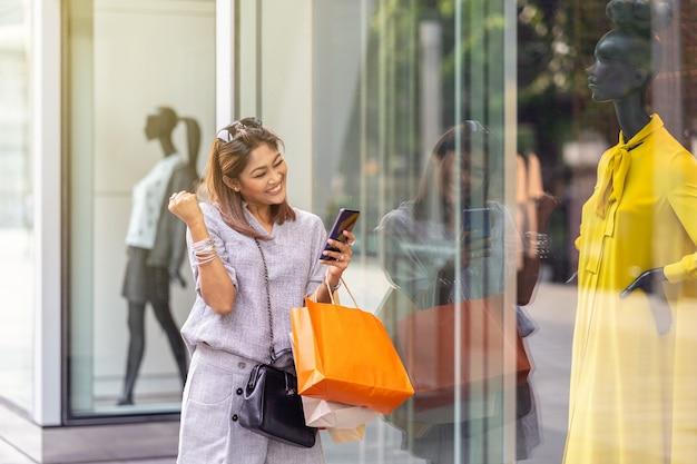 Die asiatische frau, die beim verwenden des intelligenten handys für scheckon-line-einkaufsauftrag nett ist, ist
