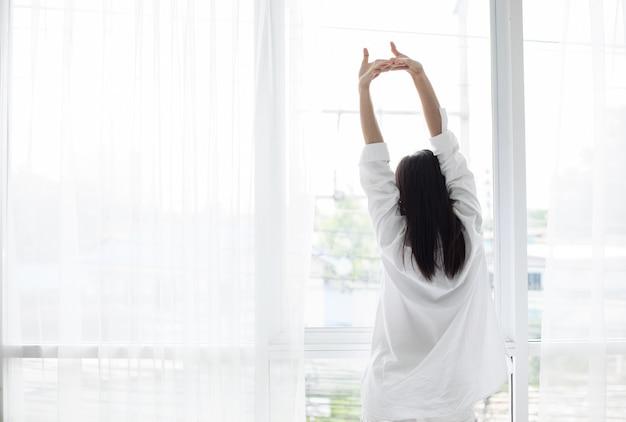 Die asiatische frau, die in ihrem bett völlig ausgeruht aufwacht und öffnet die vorhänge morgens, um frischluft zu erhalten.