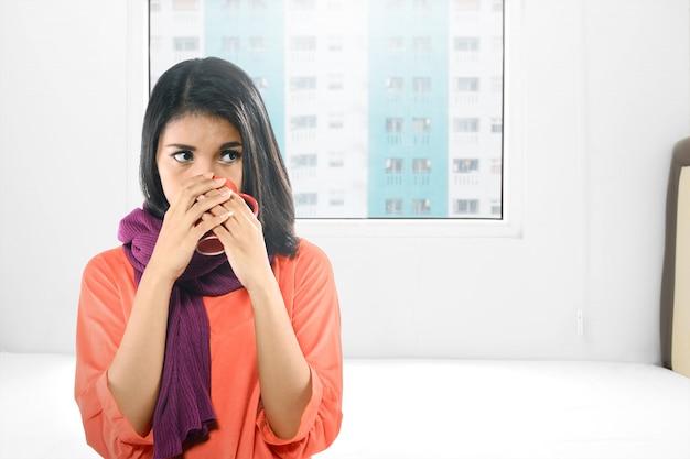 Die asiatische frau, die mit grippe krank wird, trank den heißen tee
