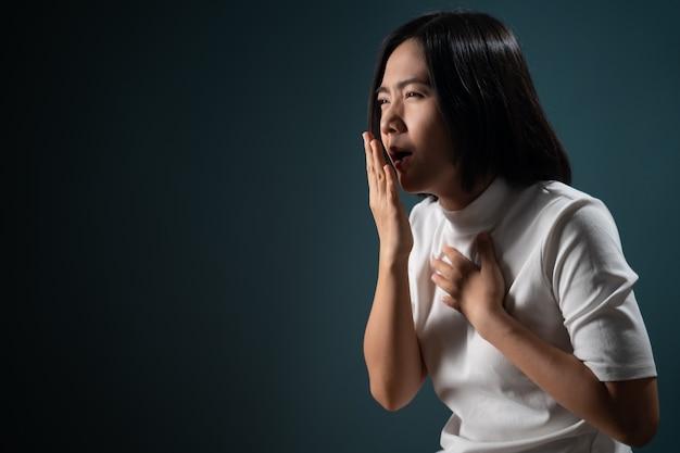 Die asiatische frau hatte halsschmerzen und stand isoliert über blau