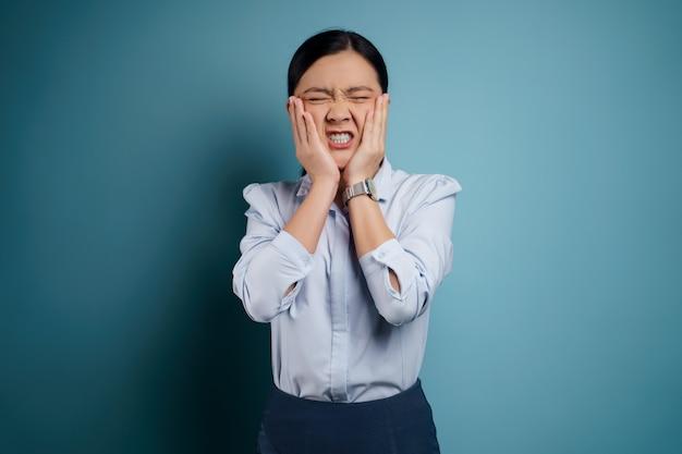 Die asiatische frau hatte zahnschmerzen, die ihre wange berührten