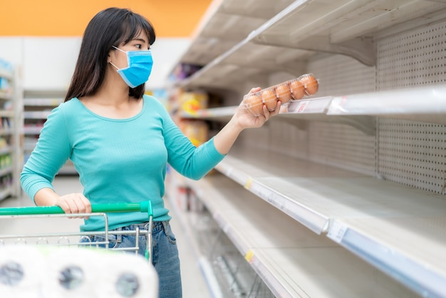 Die asiatische frau holt die letzte eierpackung in den leeren regalen des supermarkts ab, inmitten der covid-19-coronavirus-ängste, der panik der käufer beim kauf und der bevorratung von toilettenpapier, das sich auf eine pandemie vorbereitet.