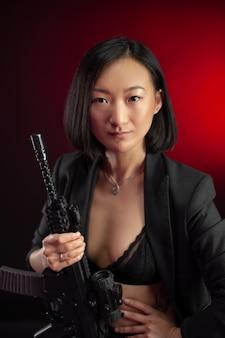 Die asiatische frau in einer jacke mit einem automatischen gewehr in den händen mafia-kämpfer