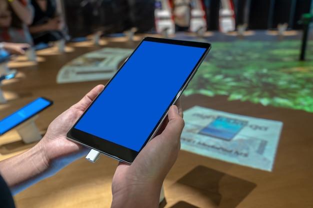 Die asiatische frauenhand der nahaufnahme, die die neue tablette im beweglichen speicher mit restlicht hält, verzieren.