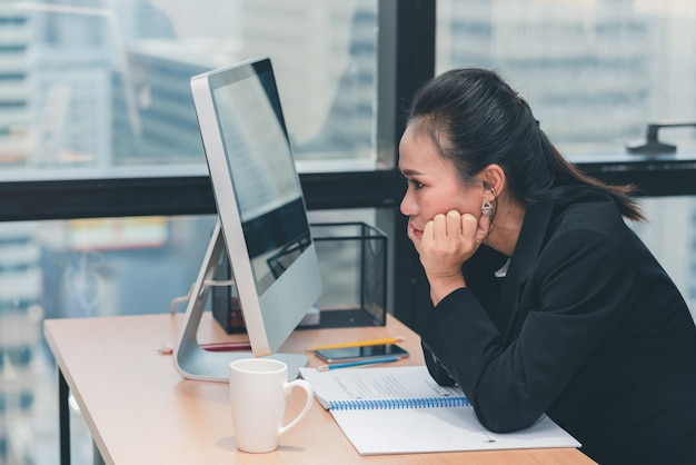 Die asiatische geschäftsfrau, die im computer und im sitzen schaut, langweilte ihre arbeit im büro