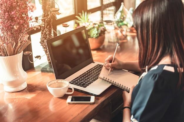 Die asiatische geschäftsfrau, die mit arbeitet, machen eine anmerkung mit einem notizbuch und einem laptop