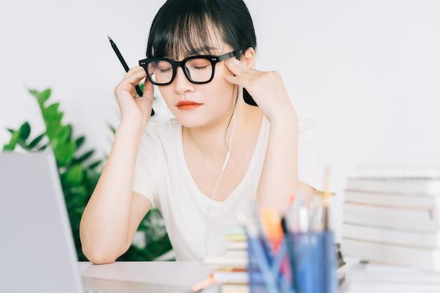 Die asiatische geschäftsfrau ist müde und hat kopfschmerzen mit viel arbeit an der frist