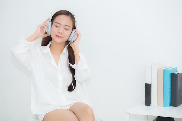 Die asiatische glückliche frau des schönen porträts genießen und spaß hören musik mit kopfhörer