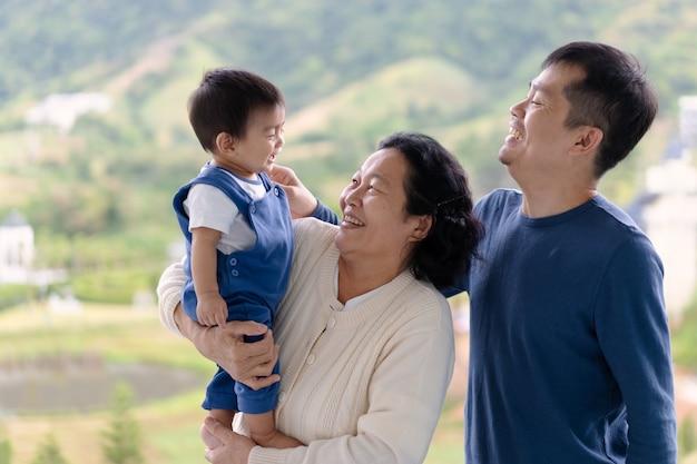 Die asiatische großmutter hält den kleinen enkel und den jungen, der mit dem vater lacht.