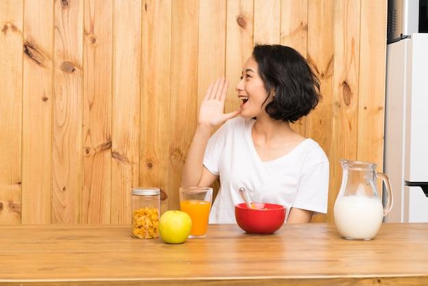 Die asiatische junge frau, die frühstücksmilch schreit mit dem breiten mund hat, öffnen sich