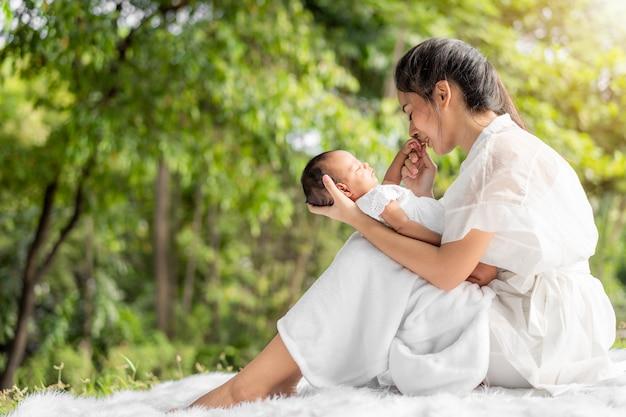Die asiatische junge schöne mutter, die sie neugeboren hält, schläft