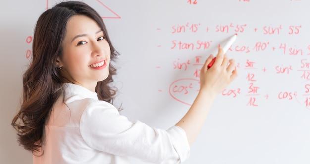 Die asiatische lehrerin schreibt die vorlesung an die tafel