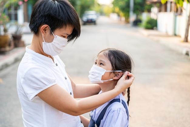Die asiatische mutter hilft ihrer tochter, eine medizinische maske zu tragen, um die situation des schutzes von covid 19 oder corona-virus zu schützen.
