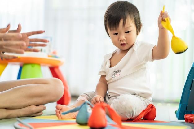 Die asiatische mutter und baby, die weichen pfeil des spielzeugs auf die mittelpfeilscheibe zeigt mutter setzt, ist hinter dem erfolg des kindes.