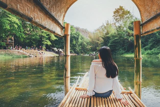 Die asiatische schönheit, die auf ein hölzernes floß reist, kreuzen hinunter die flüsse von ländlichem thailand mit grünem waldhintergrund.