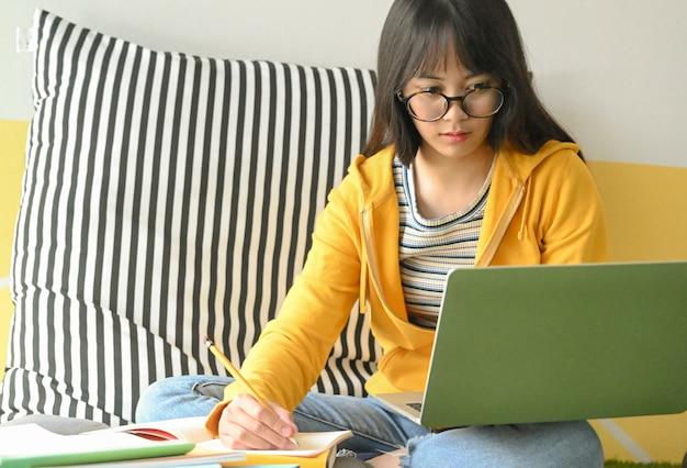 Die asiatische studentin, die gläser trägt, erforscht mit einem laptop und nimmt kenntnisse, um einen bericht zu machen.