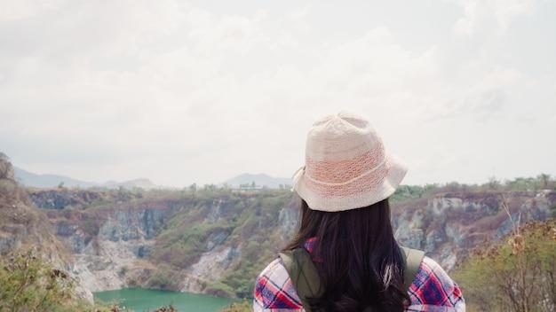 Die asiatische wandererfrau des wanderers, die zur spitze des berges geht, frau genießen ihre feiertage auf dem wandernden abenteuer, das freiheit glaubt.