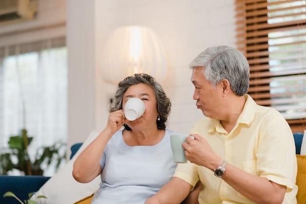 Die asiatischen älteren paare, die warmen kaffee trinken und zu hause im wohnzimmer zusammen sprechen, paare genießen liebesmoment beim auf sofa liegend, wenn sie zu hause entspannt werden.