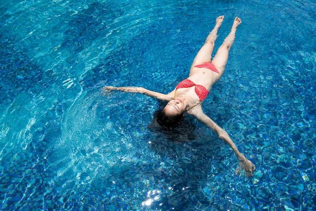 Die asiatischen frauen, die am pool schwimmen, entspannt sie sich.