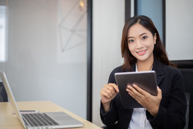Die asiatischen geschäftsfrauen, die tablette für das arbeiten im büro verwenden, entspannen sich zeit und das lächeln