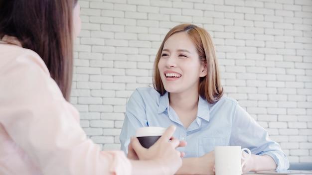 Die asiatischen geschäftsfrauen, die warmes kaffee trinkend genießen, besprechen sich über arbeit und geschwätz-klatsch