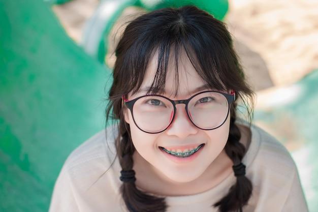 Die asiatischen jugendlichen, die gläser und klammern tragen, genießen im bunten spielplatz