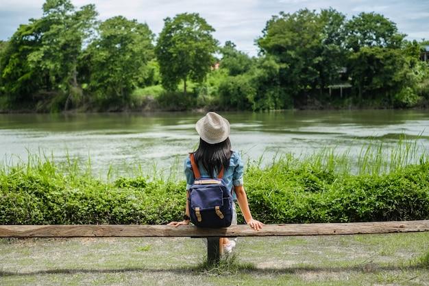 Die asien-frau, die herein den fluss betrachtet, entspannen sich zeit