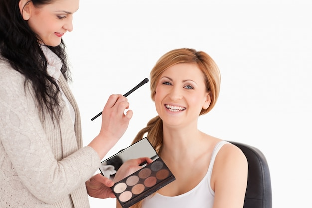 Die attraktive blond-haarige frau, die sie hat, bildete sich durch einen make-upkünstler