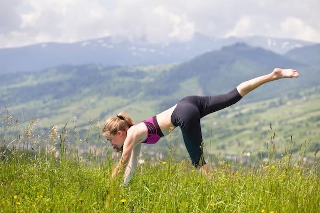 Die attraktive dünne junge frau, die yoga tut, trainiert draußen