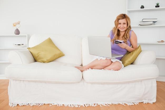 Die attraktive frau, die auf einem sofa sitzt, macht eine zahlung im internet beim sitzen auf einem sofa