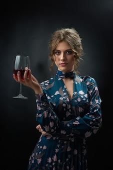 Die attraktive frau, die blaues modernes kleid mit stilvollem blumendruck trägt, hält glas voll vom rotwein.