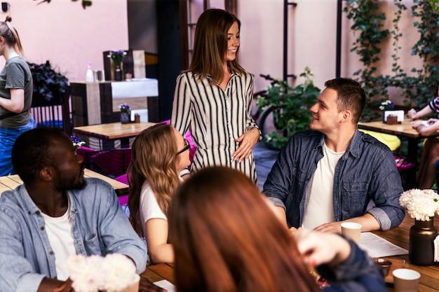 Die attraktive junge frau kommt zum wöchentlichen informellen teamtreffen im örtlichen café