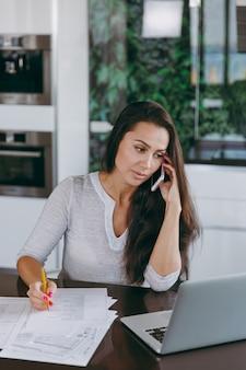 Die attraktive junge moderne geschäftsfrau, die mit dem handy spricht und mit dokumenten und laptop in der küche zu hause arbeitet