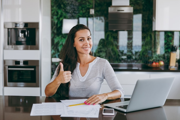 Die attraktive junge moderne geschäftsfrau zeigt die daumengeste cool und arbeitet zu hause mit dokumenten und laptop in der küche